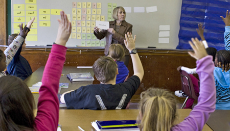 Teacher with students raising hands in a Just Words classroom