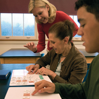 Teacher using letter tiles with two adults