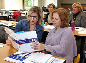 Two teachers looking at a WRS Instructor Manual (Steps 1-6), 4th Edition, during an institute
