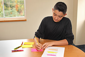 Boy using highlighters to color-code notes