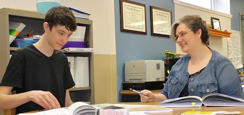 WRS teacher with student using magnetic letter tiles