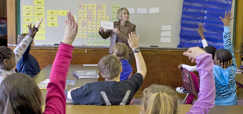 Teacher holding up a word card to her Just Words Class